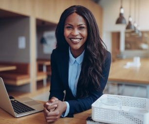 Smiling young African American businesswoman leaning on a table in an office lounge working on a laptop