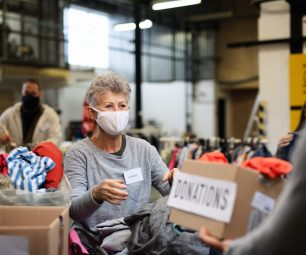 Portrait of volunteers sorting out donated clothes in community charity donation center, coronavirus concept.