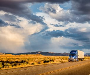 Beautiful panorama view of classic semi trailer truck on empty highway with dramatic sky in golden evening light at sunset